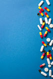 Pills border over blue Stock Photos
