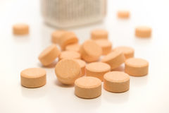 Pills and a bottle. A few capsules in front of the bottle, front capsules are in focus while the bottle is out of focus stock photo
