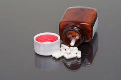 Pills and bottle. Pills / capsules spilling out of bottle onto reflective surface Stock Images