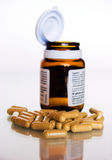 Pills and bottle. Bunch of pills in foreground and blurred open bottle in background Royalty Free Stock Photo