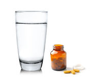 Pills from bottle and Glass of water on white backgroun Stock Images