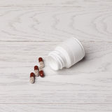 Pills with bottle. On white wooden table Royalty Free Stock Photos