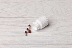 Pills with bottle. On white wooden table Royalty Free Stock Photo