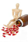 Pills from bottle  and wooden model dummy Royalty Free Stock Image