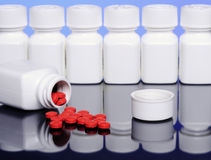 Pills and Bottles. This is part of a series of four photographs depicting red pills spilling out of the bottle, with bottles in the background. The file also Royalty Free Stock Photos