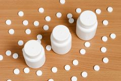 Pills and bottles on wooden surface Royalty Free Stock Photography