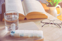 A pills box with drug for week and water in glass on table ,need. A pills box with drub for week and water in glass on table ,need some drug after hard reading Royalty Free Stock Image
