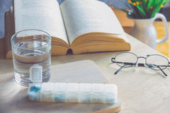 A pills box with drug for week and water in glass on table ,need. A pills box with drub for week and water in glass on table ,need some drug after hard reading Royalty Free Stock Photography