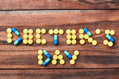 Pills on brown wooden surface. Stock Photo