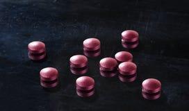 Pills of burgundy color on a mirror black surface. Selective focus stock photos