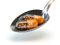 Pills with calcio calcium CA element in the spoon. Dietary suppl Stock Images