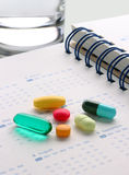 Pills on calender. ( in notebook) with glass Royalty Free Stock Images
