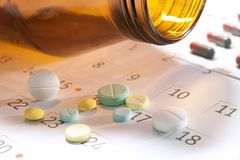Pills and calender. Pill pouring on the calender Stock Photography