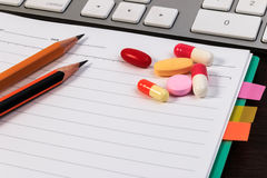 Pills, capsule, notebook, pencils and computer keyboard on wooden table. Stock Photos