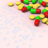 Pills and capsules on chemical diagram Stock Image