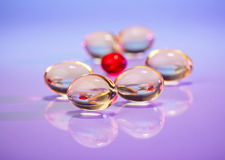 Pills (capsules) of cod-liver oil on violet Royalty Free Stock Photo