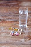 Pills and capsules with glass of water on table Royalty Free Stock Images