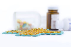 Pills and capsules and medicine bottles. Pills and capsules formed in a cross shape with medicine bottles in the background Royalty Free Stock Photos