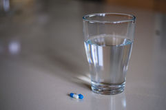 Pills capsules medicine and glass of water Royalty Free Stock Photo