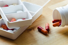 Pills, capsules and tablets sorted in pillbox Stock Photos