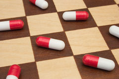 Pills on chessboard. Close-up Royalty Free Stock Image