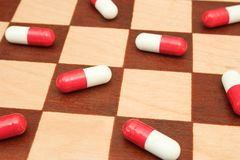 Pills on chessboard Stock Image