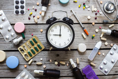 Pills and clock on table, top view. Pills and clock on table, healthy concept Royalty Free Stock Photos