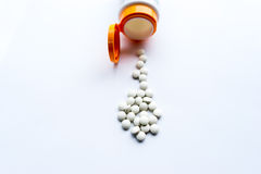 Pills coming out of medicine bottle, on white background Stock Image