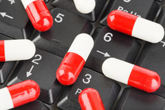Pills on computer keyboard. Concept technology background Royalty Free Stock Image