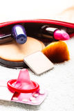 Pills, condom and cosmetics in handbag. Stock Image