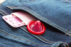 Pills and condom in denim pocket. Stock Photo