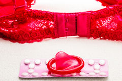Pills and condom with lace lingerie. Royalty Free Stock Images