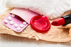 Pills condom and lipstick on lace lingerie Stock Photography