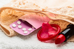 Pills condom and lipstick on lace lingerie Stock Photos