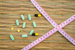 Pills and cross measuring tape on traditional mat. diet or lose Stock Photo