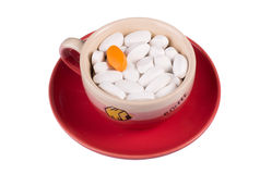 Pills in a cup of coffee. On a red saucer isolated on white Stock Photo