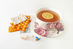 Pills and a cup of lemon tea. Cup of tea with lemon and a lot of medicines  on white - curing cold symptoms Royalty Free Stock Photo