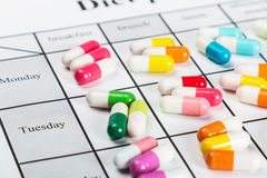 Pills of different colors on a calendar Stock Photo