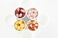 Pills/drug. White pill boxes and colored pills on a white background Stock Image