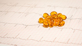 Pills on EKG. Omega 3 placed on an EKG test result - Electrocardiogram Stock Photos