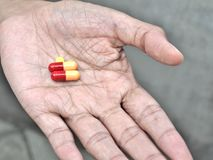 Pills on elder hand Royalty Free Stock Photography