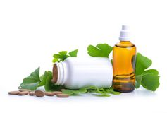 Pills with extract from the ginkgo in bottle and green leaves. Royalty Free Stock Photo