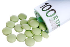 Pills fall out a sheaf of 100 euro. Green round pills fall out a sheaf of 100 euro papers Royalty Free Stock Photography