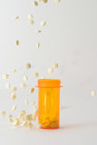 Pills falling into and around medicine bottle. Medicine bottle on table with white tablets falling into and around it; bottle is placed in the center of the royalty free stock image