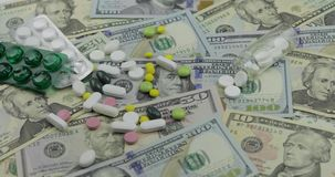 Pills falling on dollar banknotes, expensive medication, pharmaceutical business. Investment in hospitals, high price treatment, medical consumerism. Drugs stock video footage