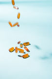 Pills falling down. Gel Capsules.  Vitamin A, E, fish oil, primr Royalty Free Stock Photography