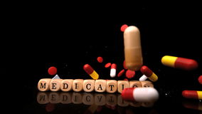 Pills falling and rolling over dice spelling medication stock video