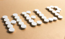 "Pills forming the word ""HELP"". Pills forming the word ""HELP"" on a beige background stock photography"
