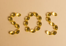 "Pills forming the word ""SOS"". Pills forming the word ""SOS"" on a beige background royalty free stock photography"