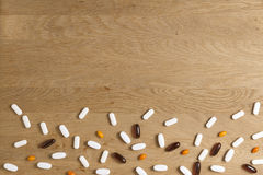 Pills frame on wooden background. Vitamins, dietary supplements, drugs, tablets on wooden table. Pharmacy, medicine and. Vitamins, supplements, drugs, tablets Royalty Free Stock Image